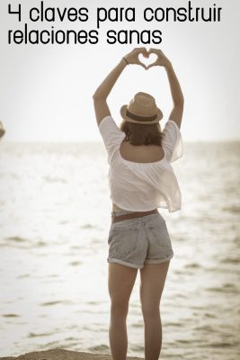 woman-standing-on-beach-showing-heart-sign-2918563